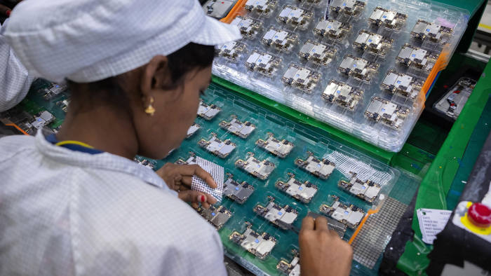 An employee assembles and inspects mobile phone parts at Rising Stars Mobile India Pvt. Ltd. at Sri City in the state of Andhra Pradesh in India on Thursday, 11th July, 2019. Photographer-Karen Dias/Bloomberg   An employee works at the factory of Rising Stars Mobile India Pvt., a unit of Foxconn Technology Co., in Sri City, Andhra Pradesh, India, on Thursday, July 11, 2019. Foxconn, also known as Hon Hai Precision Industry Co., opened its first India factory four years ago, it now operates two assembly plants with plans to expand those and open two more. The company was integral to China's transformation into a manufacturing colossus, and founder Terry Gou has told India's Prime Minister Narendra Modi that Foxconn could help India do the same. Photographer: Karen Dias/Bloomberg