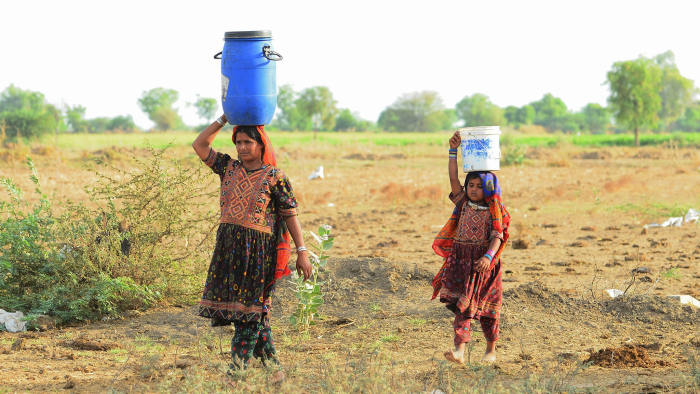 Migrant shepherds in Gujarat carry water to their camp