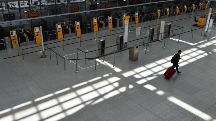 """TOPSHOT - A passenger walks in an empty Lufthansa terminal at the """"Franz-Josef-Strauss"""" airport in Munich, southern Germany, on May 27, 2020. - Coronavirus-stricken airline group Lufthansa wavered on May 27, 2020 on grabbing a nine-billion-euro ($9.9 billion) German state lifeline, throwing up new turbulence for a rescue that could decide the fate of the historic company. (Photo by Christof STACHE / AFP) (Photo by CHRISTOF STACHE/AFP via Getty Images)"""