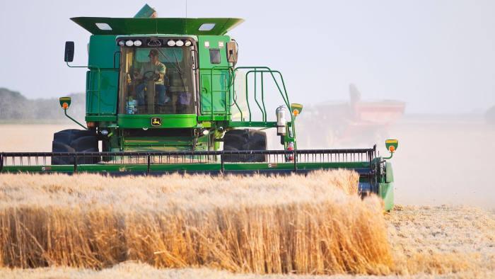 BP3FNN Combine harvesting wheat crop on the Canadian Prairies. Near Winkler, Manitoba, Canada.