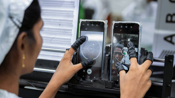 An employee tests the camera quality of mobile phones on an assembly line in the mobile phone plant of Rising Stars Mobile India Pvt., a unit of Foxconn Technology Co., in Sri City, Andhra pradesh, India, on Thursday, July 11, 2019. Foxconn, also known as Hon Hai Precision Industry Co., opened its first India factory four years ago, it now operates two assembly plants with plans to expand those and open two more. The company was integral to China's transformation into a manufacturing colossus, and founder Terry Gou has told India's Prime Minister Narendra Modi that Foxconn could help India do the same. Photographer: Karen Dias/Bloomberg