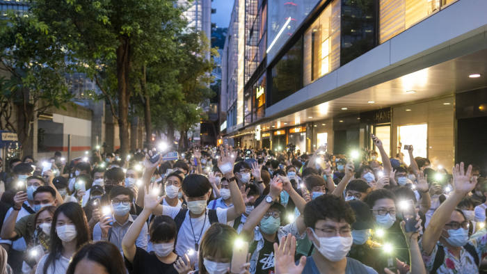 Demonstrators shine lights from smartphones as they march during a protest in the Central district of Hong Kong, China, on Tuesday, June 9, 2020. Hundreds of protesters converged on Hong Kong's Central business district, defying police warnings of unlawful assembly to mark the one-year anniversary of the first major march against since-scrapped legislation allowing extradition to China. Photographer: Justin Chin/Bloomberg