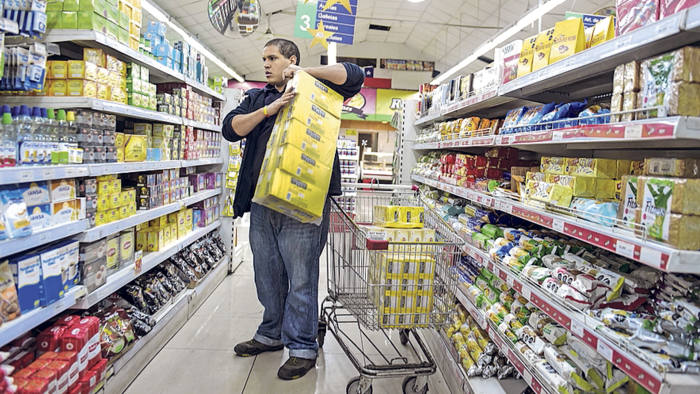 An employee of a supermarket places on the shelves food packages with their labels that comply with the new regulations, in Santiago, on June 20, 2016. A new law coming into force next week makes mandatory for food to have printed clearly in their labels whether they have high content of saturated fat, sugar, sodium as their respective caloric values. / AFP / MARTIN BERNETTI (Photo credit should read MARTIN BERNETTI/AFP/Getty Images)