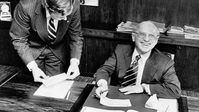 Nobel winning economist Milton Friedman receives his prize sum of $150,000 (U.S.) at PKbanken in Stockholm, from Claes G. Tisell, left, Dec. 13, 1976. Mr. Tisell is regional manager for Pkbanken in North America. (AP Photo/Reportagebild)