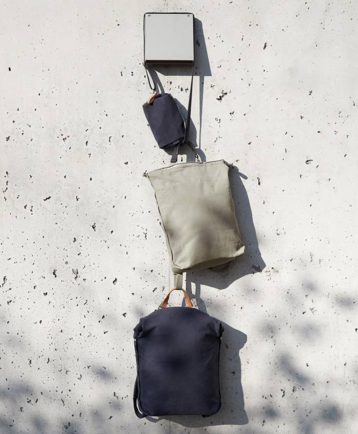 QWSTION navy hip pouch, €70, limestone zip pack, €275, and navy roll pack, €295