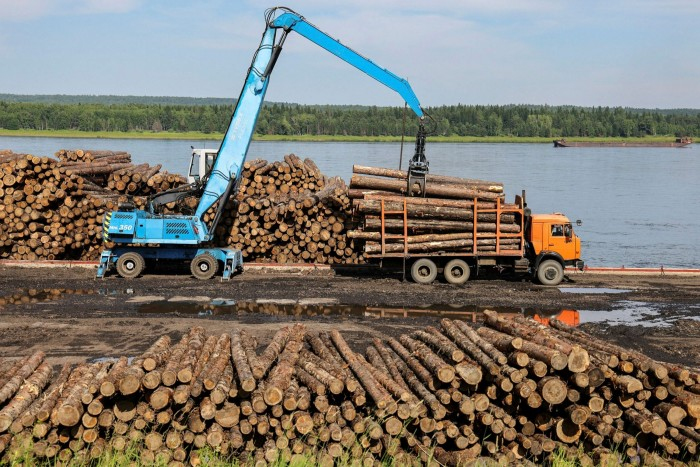 A truck-mounted log loader lifts logs from a barge docked on the banks of the Yenisei River