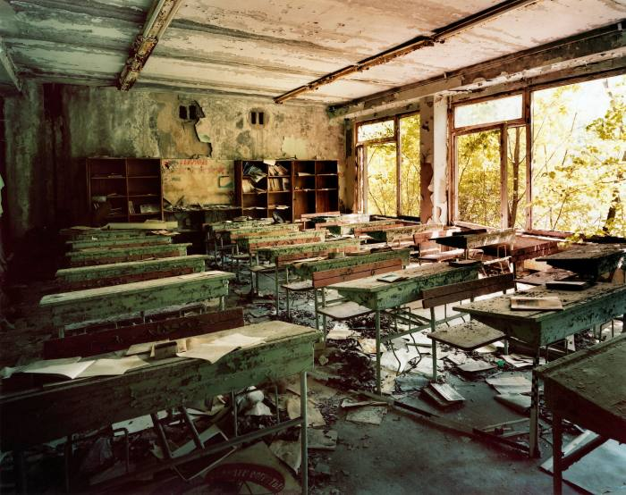 A classroom is recognisable but totally wrecked. Pale light comes through a window