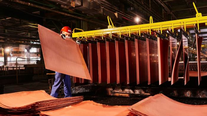 A worker handles newly formed copper cathode sheets in a warehouse