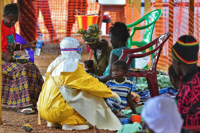 A medical worker feeds a child diagnosed with Ebola virus, in Kailahun, Sierra Leone