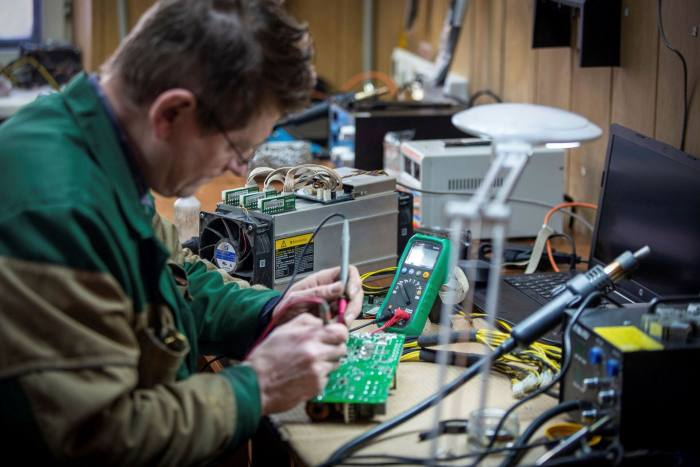 A technician repairs cryptocurrency mining hardware