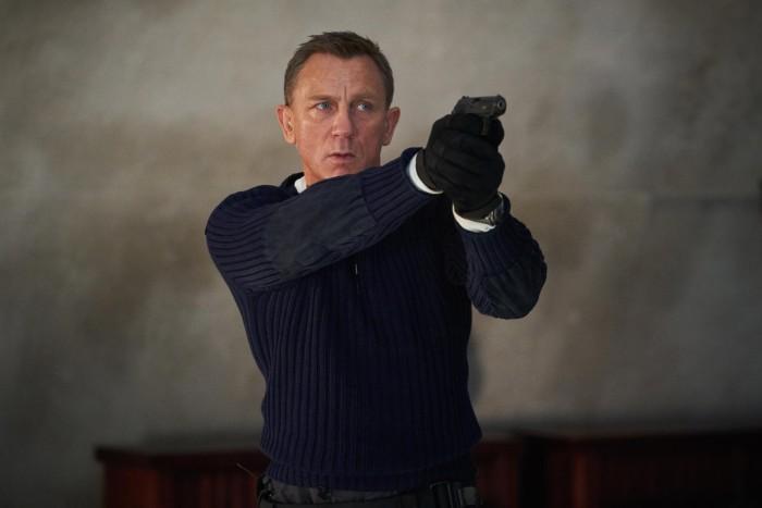 Daniel Craig wears a navy N.Peal army sweater in No Time to Die