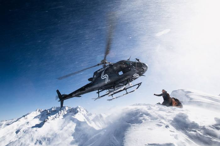 A helicopter lifts off after dropping a group of skiers
