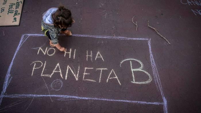 A child in Barcelona alongside graffiti reading 'There is no planet B'