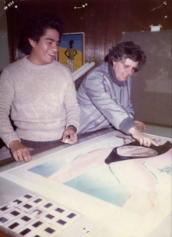 A young man next to an older woman who is pointing at an artwork of a woman in a bikini on a table