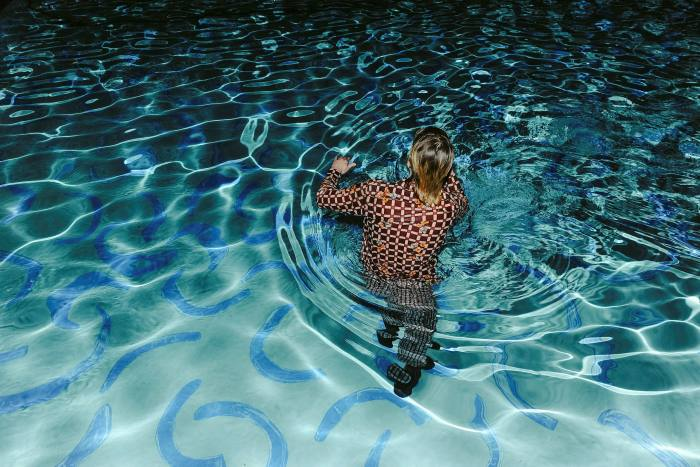 A person wades into the pool, which has blue painted curves on the bottom