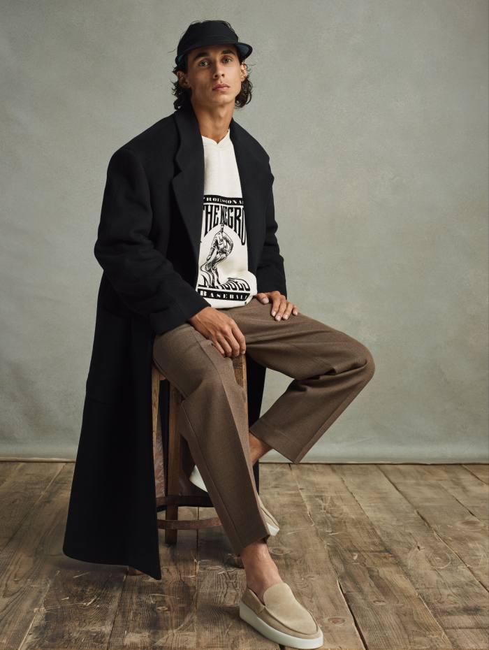 Fear of God wool overcoat, $2,550, fleece sweatshirt, $595, wool trousers, $850, and leather visor, $250