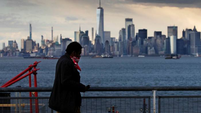 A passenger wearing a mask enters the St. George Ferry Terminal from the Staten Island borough of New York