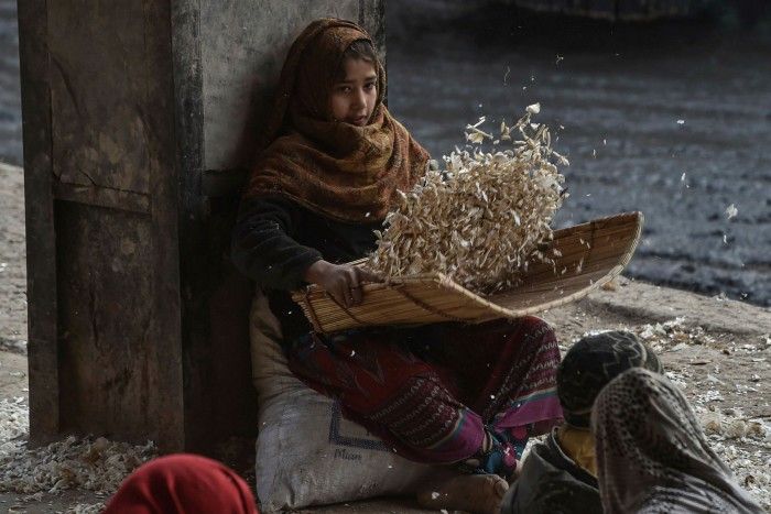 A child cleaning garlic in a market in Lahore, Pakistan