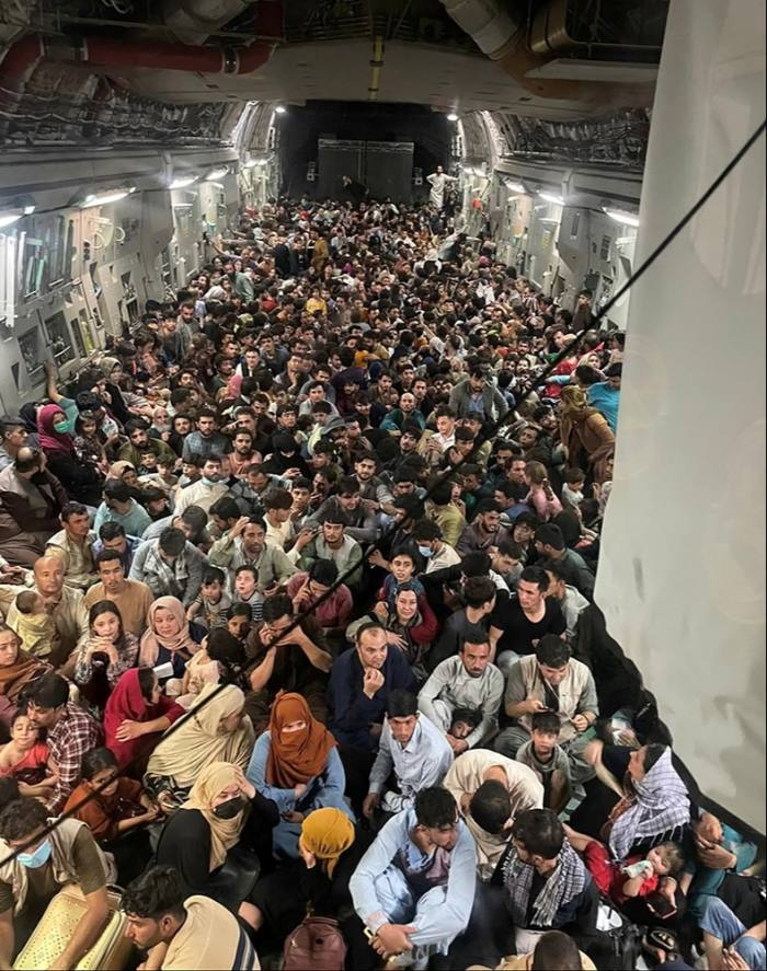 Afghans crowding on to a US C-17 Globemaster III flying 640 evacuees to Qatar, August 15