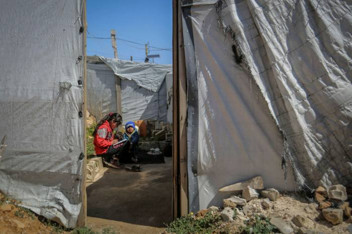 Syrian siblings outside their tent at a refugee camp in the Lebanese town of Aarsal