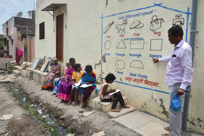 A teacher in India's Maharashtra state holds an outdoor lesson for pupils unable to join classes online