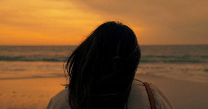 A woman's head from behind in front of the ocean at sunset