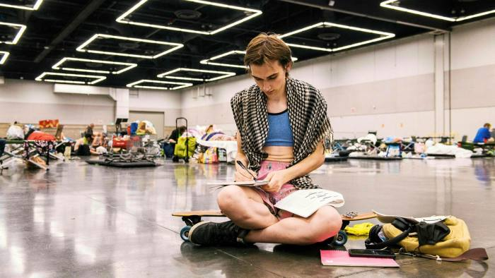 A woman writes on a notebook as people rest at the Oregon Convention Center cooling station in Portland, after a heatwave moved through the region