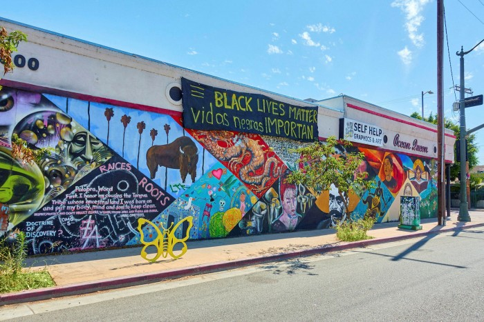 View along a one-storey building frontage brightly painted with animals and plants. Banners hang from the top, one says Black Lives Matter