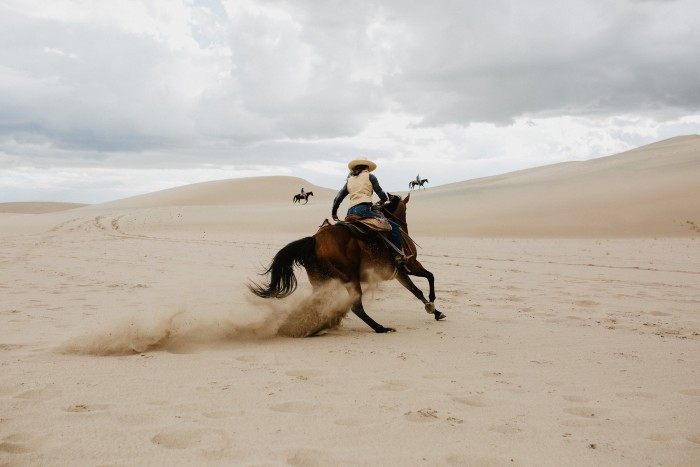 Wranglers ride in the Great Sand Dunes National Park that neighbours Zapata Ranch
