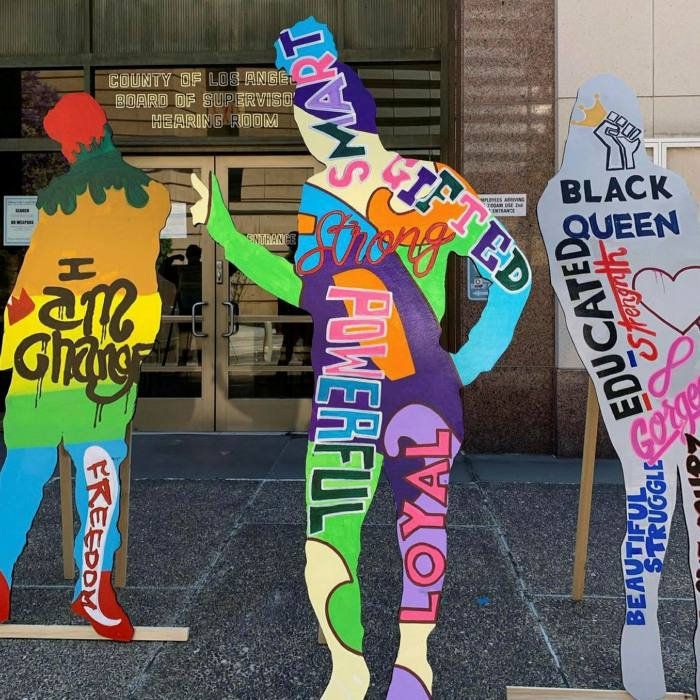 Three flat human-size and human-shaped figures brightly painted in rainbow colours