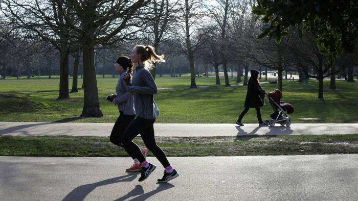 Two women run in Victoria Park in East London during lockdown 3