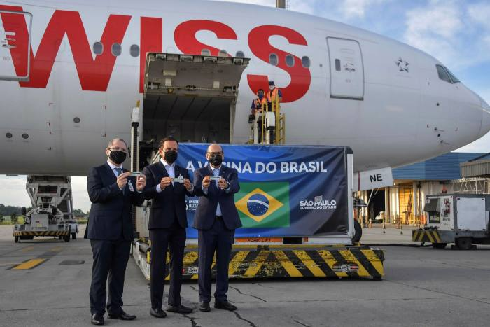Brazilian officials at SãoPaulo airport next to a container carrying vaccines from China