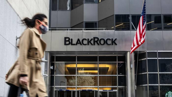 A pedestrian wearing a protective mask passes in front of BlackRock in New York