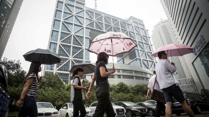 Pedestrians walk past the Shanghai Stock Exchange