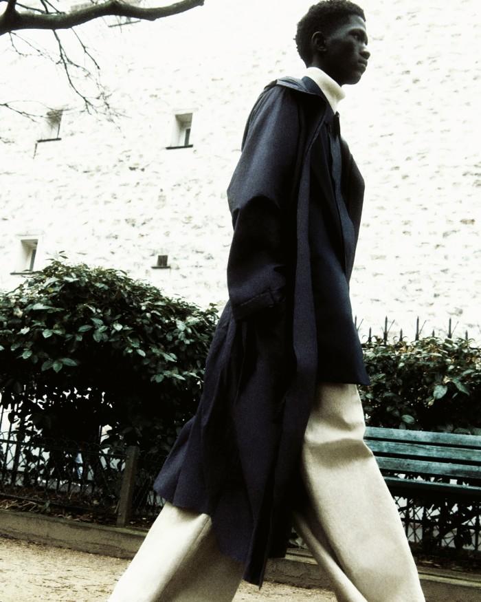 Moustapha wears Craig Green cotton Kimono parka, POA. Herno bi-stretch technical fabric raincoat (seen underneath), £650. Uniqlo merino wool rollneck, £30. Bottega Veneta natural linen canvas trousers, £905