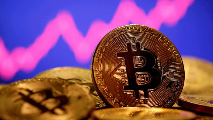 Representation of virtual currency bitcoin seen in front of a stock graph