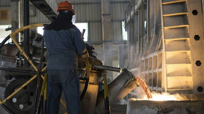 A worker pours molten aluminium at a smelting facility in China